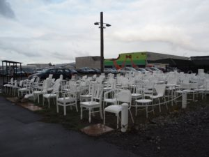 Rows of white chairs, by a temporary carpark