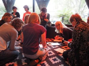 group of people sitting on carpeted floor, discussing taste and appearance of dried herbs